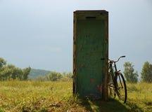 Gammal cykel nära gammalt telefonbås arkivbild