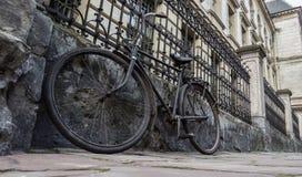 Gammal cykel som parkeras mot staketet och ett gammalt hus Arkivfoto