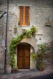 Gammal dörr i den Tuscany staden av Assisi Arkivbild