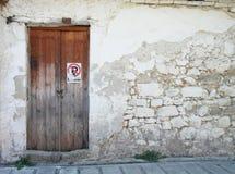Gammal dörr med den vita för Grekland för stenvägg staden lefkas Royaltyfri Foto