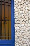 Gammal dörr med fasaden som göras med hav rundade stenar Arkivbild