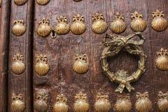 Gammal dörr med guld- smidesjärndetaljer med diagram av skal arkivbild