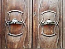 Gammal dörr med polerade metallhandtag och krökta garneringar Arkivfoton