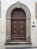 Gammal dörr med polerade metallhandtag och krökta garneringar Fotografering för Bildbyråer