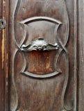 Gammal dörr med polerade metallhandtag och krökta garneringar Arkivbilder