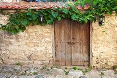 Gammal dörr och vinranka på stenväggen, Nessebar Royaltyfri Foto