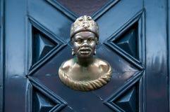 Gammal dörrhandtag i form av manhuvudet på en blå dörr arkivfoton