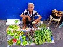 Gammal dam i en marknad i cainta, rizal, philippines som säljer frukter och grönsaker arkivfoton
