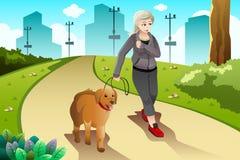 Gammal dam som övar med hennes utomhus- hund Arkivfoton