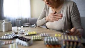 Gammal dam som känner sig opasslig och att söka efter preventivpillerar, sjukt problem för kvinnalidandehjärta royaltyfri foto