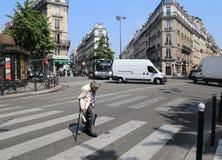 Gammal dam som korsar vägen i Paris fotografering för bildbyråer