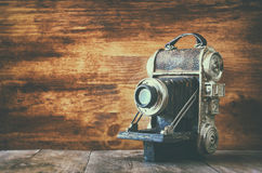 Gammal dekorativ kamera för tappning på brun träbakgrund Rum för text Royaltyfri Foto