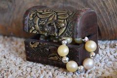 Gammal dekorativ smyckenask och en vit pärlemorfärg halsband, en resväska med en skatt Royaltyfria Foton