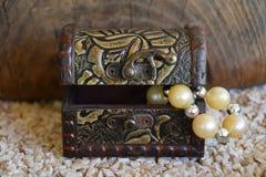 Gammal dekorativ smyckenask och en vit pärlemorfärg halsband, en resväska med en skatt Fotografering för Bildbyråer