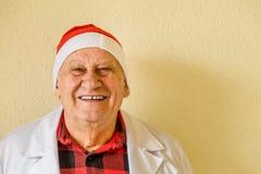 Gammal doktor med den Santa Claus hatten arkivbild