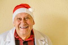 Gammal doktor med den Santa Claus hatten royaltyfri fotografi