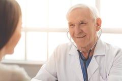 Gammal doktor och patient arkivbild
