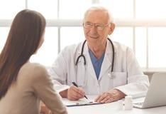 Gammal doktor och patient royaltyfria foton