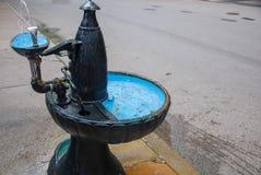 Gammal dricka springbrunn med blåa bunkar royaltyfria bilder