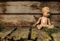 Gammal eftersatt docka framme av ett herrelöst godsskjul arkivfoto