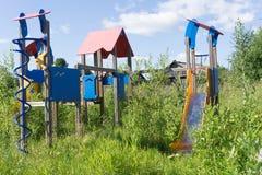 Gammal eftersatt lekplatsutrustning som är bevuxen med weeds royaltyfria bilder
