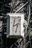 Gammal electroguard mot bakgrunden av de förvirrade trådarna på en gammal träkolonn close upp arkivfoton
