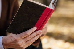 Gammal elegant man som utanför läser en bok Arkivfoton