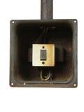 Gammal elektrisk strömbrytare i den rostiga metallasken på en vit bakgrund Arkivfoton
