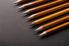 Gammal en och överflöd av nya blyertspennor på svart bakgrund Arkivfoto