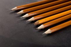 Gammal en och överflöd av nya blyertspennor på svart bakgrund Royaltyfri Fotografi