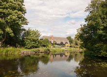 Gammal engelsk historisk stuga som ses över en sjö med reflexioner royaltyfria bilder