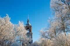 Gammal ensam kyrka i träden som täckas med snö Royaltyfri Bild