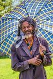 Gammal ethiopian man med ett paraply på en varm dag Royaltyfri Bild