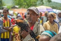 Gammal ethiopian man som säljer en tupp i en marknad Royaltyfria Bilder