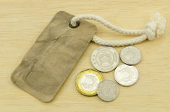 Gammal etikettsetiketttappning med mynt på wood bakgrund Royaltyfri Bild