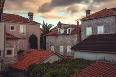 Gammal europeisk stadsgatasikt med orange tegelplattatak i antik arkitektur under härlig solnedgång i retro tappningstil arkivbilder