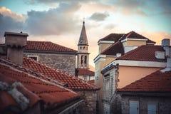 Gammal europeisk stadshorisont med orange tegelplattatak och torn framme av dramatisk solnedgånghimmel med antik arkitektur i gam arkivbild