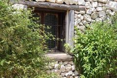 Gammal fönster och lövverk Arkivfoto