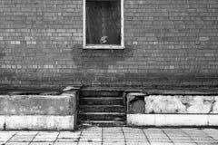 Gammal fönster- och tegelstenvägg med trappan i svartvitt Arkivbilder