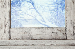 Gammal fönsterfönsterbräda framme av det drömlika vinterlandskapet arkivfoton