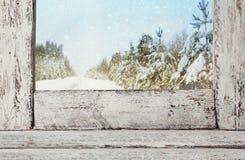 Gammal fönsterfönsterbräda framme av det drömlika vinterlandskapet arkivfoto