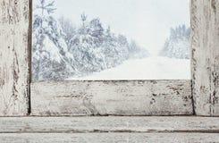 Gammal fönsterfönsterbräda framme av det magiska vinterlandskapet arkivbilder