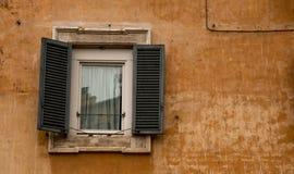 Gammal fönsteruppsättning in i ett gammalt, ockravägg arkivfoton