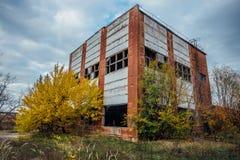 Gammal föråldrad förstörd konkret industribyggnad Övergiven fabrik i höst Royaltyfri Foto
