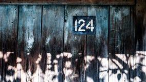 Gammal ` för hus` 124 på den gamla träväggen Royaltyfri Bild