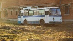 Gammal för Sovjetunionen ussr för tappningvitblått buss relik i solig sommardag i fält framme av den gula orange tegelstenväggen arkivfilmer
