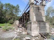 Gammal förstörd bro över flodsommaren Arkivbild