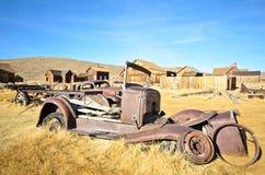 Gammal förstörd metallbil i spökstad Royaltyfri Fotografi