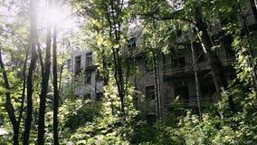 Gammal förstörd tegelstenbyggnad för fasad med brutna fönster i industriell zon av den öde staden Hus i sp?kstad stock video