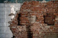 Gammal förstörd vägg med tegelstenar och tegelplattan arkivfoto
